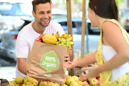 health fair: Small business owner at an open street market, selling organic fruits and vegetables to a woman carrying a shopping paper bag with a 100% organic certified label. Stock Photo