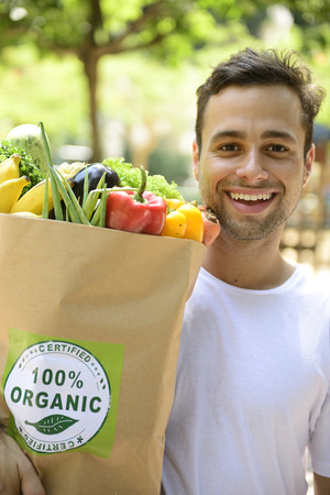 Happy man carrying bag full of organic food photo