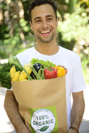 Happy man carrying a bag full of organic food. photo