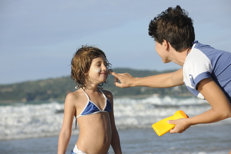 Mother applying sunscreen to daughter at beach, during a sunny summer day. photo