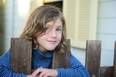 Child looking through bars of  fence with wooden house in the background smiling photo