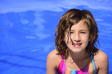 Portrait of a happy kid in the pool with copyspace photo