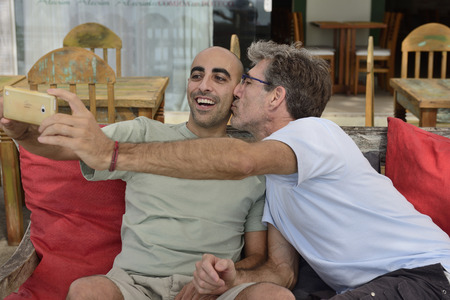 Gay couple taking a selfie with mobile phone in a cafe photo