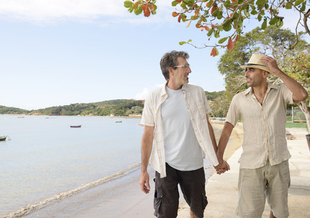 old couple walking: Travel: Gay couple on vacation holding hands