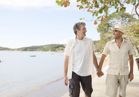 hombres gays: Viajes: Pareja gay en las manos sosteniendo vacaciones