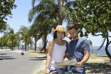 Happy tourist couple with map doing sightseeing with copy space photo