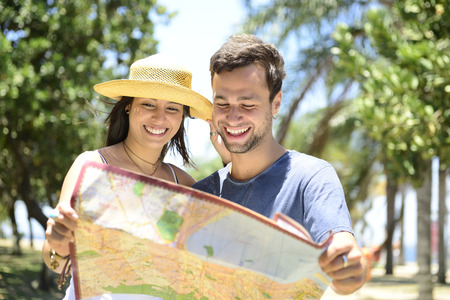 Happy tourist couple with map doing sightseeing photo