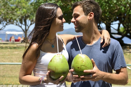 Happy couple drinking coconut water in the park photo
