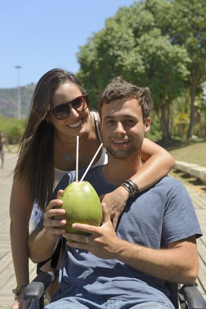 handicapped man in wheelchair and girlfriend drinking coconut water photo