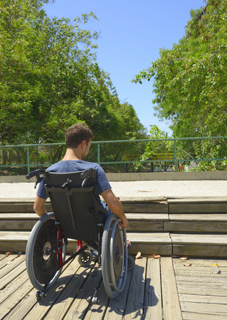 handicapped man in wheelchair in front of stairs photo