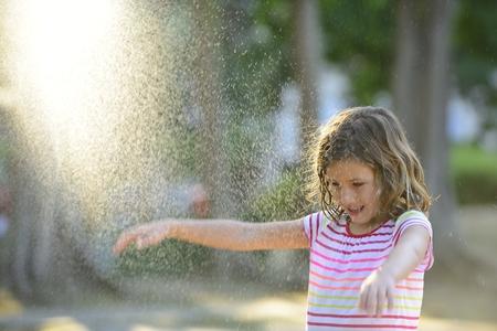 rain shower: Happy smiling girl outdoor on a sunny day enjoying the light summer rain.