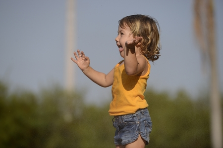 little toddler girl playing and jumping in the summer rain photo