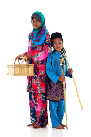 Muslim boy and muslimah girl with oil lamp during hari raya festival Stock Photo
