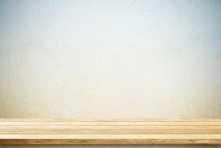 Lege houten tafel over betonnen muur.
