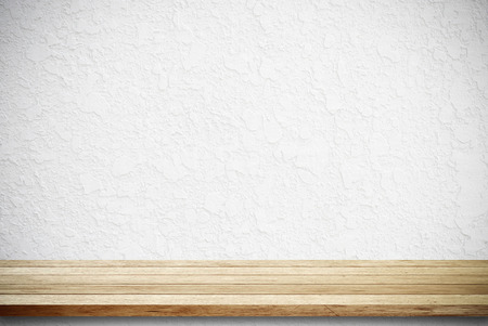 Empty wooden table over white cement wall photo
