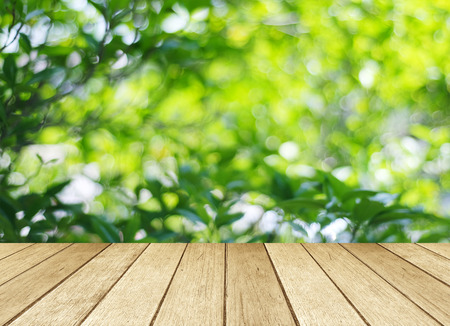 Empty wood table with blur green leaves bokeh background Imagens