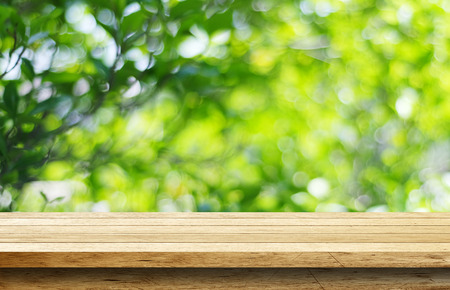 wooden desk: Empty wood table with blur green leaves bokeh background Stock Photo