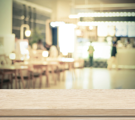 Empty wood table and blurred cafe with bokeh light background Фото со стока