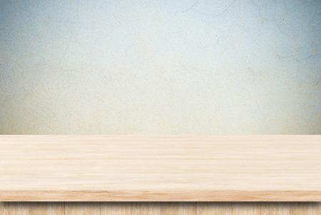 Lege houten tafel over grunge cement muur.