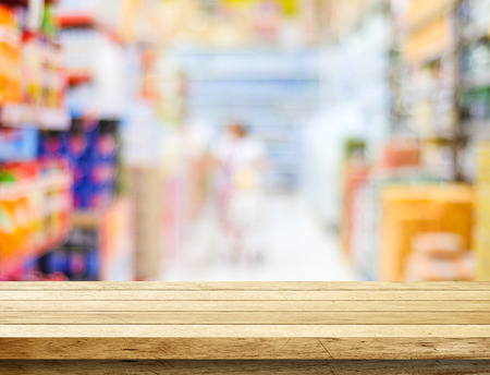 Empty table over blur supermarket with bokeh background, product display template.
