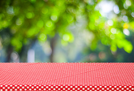 red tablecloth: Table with red tablecloth and blur trees with bokeh background