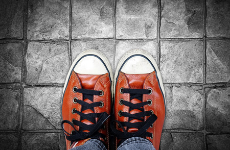converse: Feet in leather sneaker on pavement background, top view