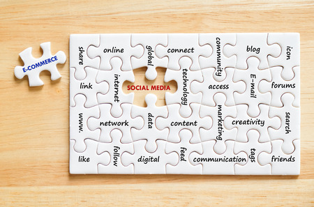 E-commerce and social media words on jigsaw puzzle background, success in business concept Stock Photo