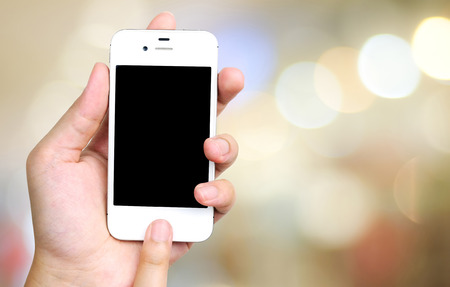 Smart phone in hand on bokeh background, technology concept