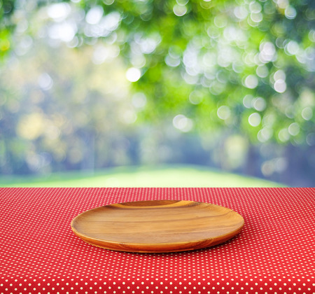 Empty round wooden tray on red polka dot tablecloth over blur trees with bokeh background, Product display montage Archivio Fotografico