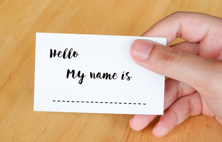 name tags: Hello my name is words on name card in hand background