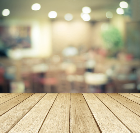 background wood: Perspective wood over blurred restaurant with bokeh background, foods and drinks, product display montage Stock Photo