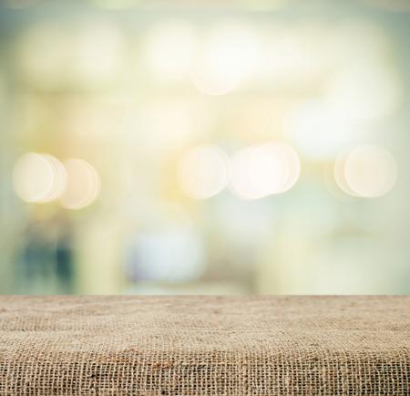 textuur: Jute over de tafel en onscherpte bokeh achtergrond, templatej product beeldscherm montage