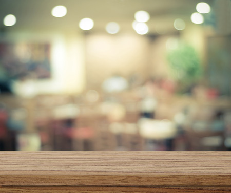 room background: Empty wood table and blurred cafe with bokeh light background, product display montage