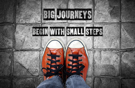 Big journeys begin with small steps, Inspiration quote, shoes on pavement Stock Photo