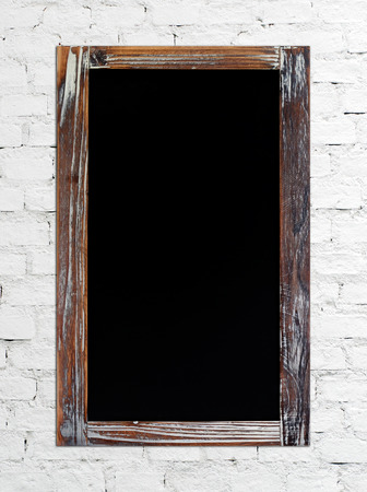 wording: Blank vintage chalk board on white brick wall, grunge background Stock Photo