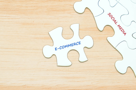 business media: E-commerce and social media words on jigsaw puzzle background, digital marketing, success in business concept
