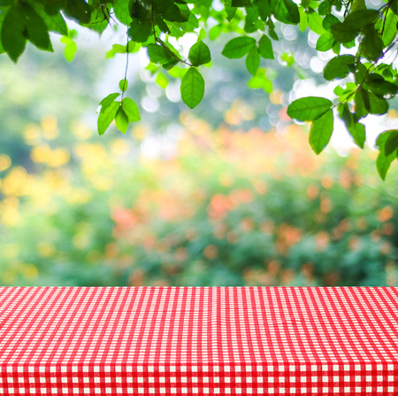Lege tafel en rode tafellaken met bokeh achtergrond wazig groene bladeren, voor product weergave montage