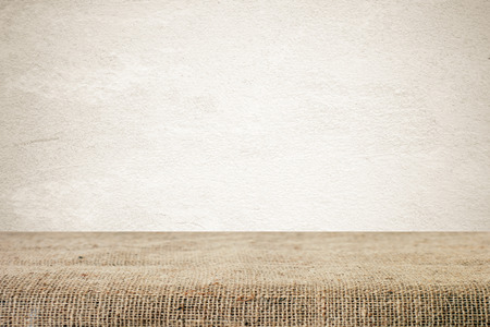 sackcloth: Empty table covered with sackcloth over grunge cement wall  background Stock Photo