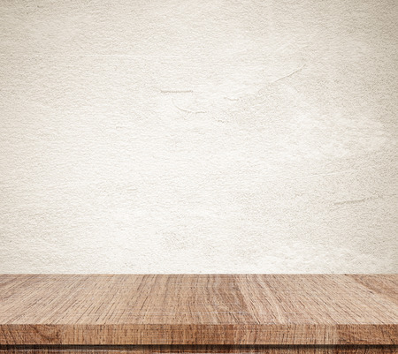 Empty wooden table over grunge cement wall Stockfoto