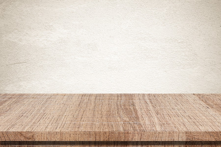 Empty wooden table over grunge cement wall Archivio Fotografico