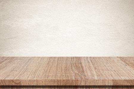 Empty wooden table over grunge cement wall Standard-Bild