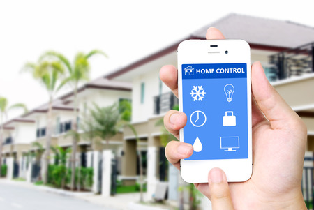 security monitoring: Hand holding white mobile smart phone with smart home application on the screen over blurred house background, smart home concept