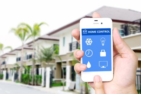monitoreo: Mano que sostiene blanco teléfono móvil inteligente con la aplicación inteligente del hogar en la pantalla sobre fondo casa borrosa, el concepto de casa inteligente