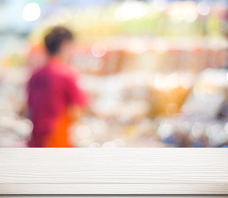 table surface: Empty white table over blur supermarket with bokeh background, product display template.