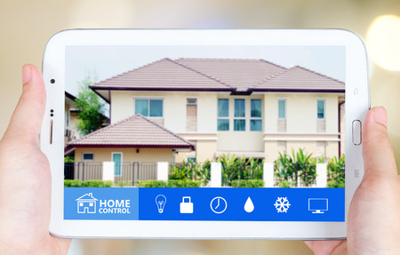 smart home: Hand holding tablet with smart home application on the screen over blurred house background, smart home concept Stock Photo