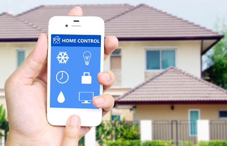 monitoring: Hand holding white mobile smart phone with smart home application on the screen over blurred house background, smart home concept