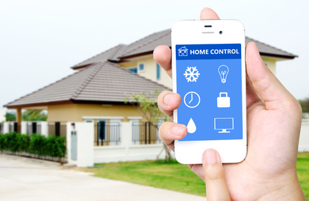 Hand holding white mobile smart phone with smart home application on the screen over blurred house background, smart home concept