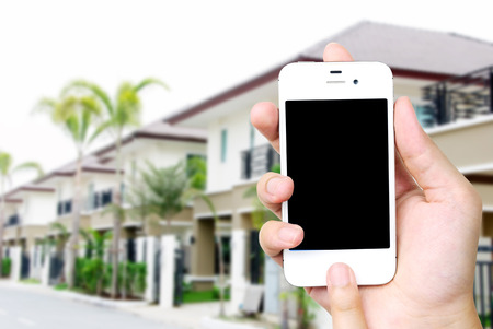 Hand holding white mobile smart phone over blurred house background, smart home concept, template, mock up