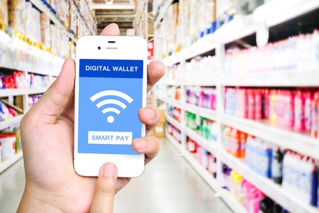 Digital wallet concept on smart phone screen over blur supermarket background, e-commerce, smart pay, business and technology concept