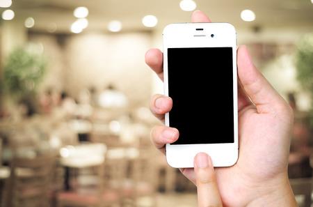 restaurant background: Hand holding smartphone over blur restaurant background, restaurant reservation, food online, food delivery concept